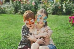 Niños, muchacho y muchacha felices con la pintura de la cara en parque Imagenes de archivo