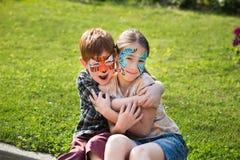 Niños, muchacho y muchacha felices con la pintura de la cara en parque Fotos de archivo