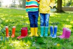 Niños, muchachos o muchachas en vaqueros y chaqueta amarilla en botas de lluvia coloridas imagen de archivo libre de regalías