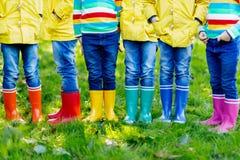 Niños, muchachos o muchachas en vaqueros y chaqueta amarilla en botas de lluvia coloridas foto de archivo