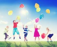 Niños multiétnicos al aire libre que juegan los globos Imagen de archivo