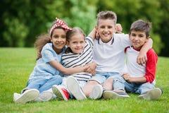 Niños multiétnicos que sientan el abarcamiento y que sonríen en la cámara en parque Imagen de archivo libre de regalías