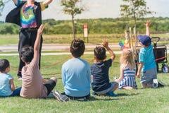 Niños multiculturales de la vista posterior en el prado de la hierba que aumenta las manos en juego al aire libre fotografía de archivo