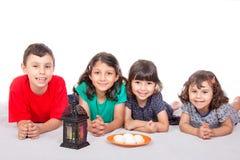 Niños musulmanes que comen Kahk - Kaak y x28; Galletas y x29; en el banquete Imagenes de archivo