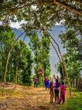 Niños nepaleses que juegan en un oscilación de bambú tradicional Foto de archivo