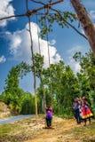 Niños nepaleses que juegan en un oscilación de bambú tradicional Imagenes de archivo