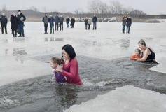 Niños, niñas con los adultos que nadan en el río en la epifanía cristiana del día de fiesta del invierno Foto de archivo