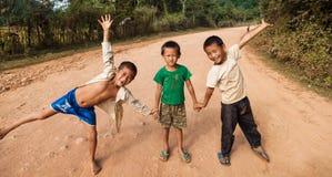 Niños no identificados que presentan en un camino en Vang Vieng Imagen de archivo libre de regalías