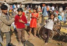 Niños no identificados que se divierten en mercado del pueblo con los amigos Fotos de archivo libres de regalías
