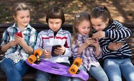 Niños ordinarios que juegan con el teléfono en banco al aire libre Foto de archivo libre de regalías