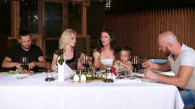 Niños, padres y amigos en una tabla al aire libre, comiendo la comida, decir las tostadas, cena de la familia en el pórtico fuera metrajes