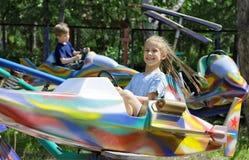 Niños, paseo en una atracción en parque Foto de archivo libre de regalías
