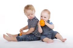 Niños pequeños con la naranja Fotos de archivo libres de regalías
