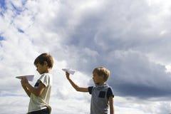 Niños pequeños con los aviones de papel contra el cielo azul Foto de archivo libre de regalías
