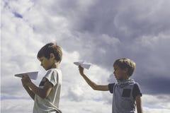 Niños pequeños con los aviones de papel contra el cielo azul Fotos de archivo