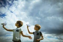 Niños pequeños con los aviones de papel contra el cielo azul Foto de archivo