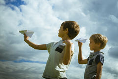 Niños pequeños con los aviones de papel contra el cielo azul Imagenes de archivo