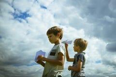Niños pequeños con los aviones de papel contra el cielo azul Imagen de archivo