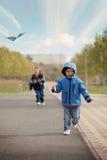 Niños pequeños, corriendo con la cometa Imagenes de archivo