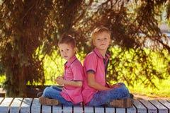 Niños pequeños del retrato dos que juegan a juegos en el teléfono móvil en soleado Foto de archivo libre de regalías