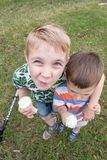 Niños pequeños divertidos de los niños de los niños que comen el helado Foto de archivo