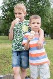 Niños pequeños divertidos de los niños de los niños que comen el helado Foto de archivo libre de regalías