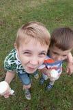 Niños pequeños divertidos de los niños de los niños que comen el helado Imagenes de archivo