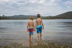 Niños pequeños en el lago de la montaña fotos de archivo libres de regalías