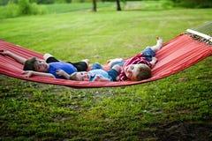 Niños pequeños en la hamaca Fotos de archivo