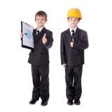 Niños pequeños en los trajes de negocios aislados en blanco Imagen de archivo libre de regalías