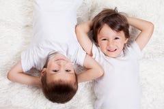 Niños pequeños felices dulces adorables que miran la cámara imagen de archivo