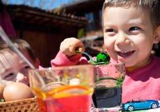 Niños pequeños felices que teñen los huevos de Pascua Imágenes de archivo libres de regalías