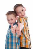 Niños pequeños - hermanos - aislados con los pulgares para arriba. Fotos de archivo libres de regalías