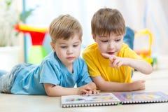 Niños pequeños leídos juntos en cuarto de niños Foto de archivo libre de regalías