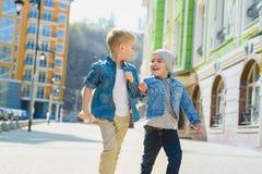 Niños pequeños lindos al aire libre en ciudad en día de primavera hermoso Imágenes de archivo libres de regalías