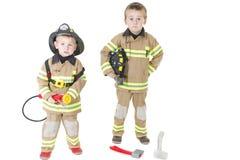 Niños pequeños lindos en el equipo del bombero imagenes de archivo