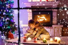 Niños pequeños lindos, gemelos rubios que juegan junto y lookinig en el fuego en chimenea Familia que celebra día de fiesta de Na Fotos de archivo libres de regalías