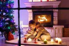 Niños pequeños lindos, gemelos rubios que juegan junto y lookinig en el fuego en chimenea Familia que celebra día de fiesta de Na Imagen de archivo libre de regalías