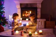 Niños pequeños lindos, gemelos rubios que juegan junto y lookinig en el fuego en chimenea Familia que celebra día de fiesta de Na Imágenes de archivo libres de regalías