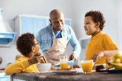 Niños pequeños lindos que charlan con su padre mientras que come el desayuno Fotos de archivo libres de regalías