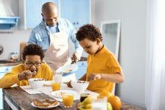 Niños pequeños lindos que comen el desayuno mientras que su padre que cocina la tortilla Imagenes de archivo