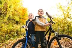 Niños pequeños lindos que completan un ciclo en parque soleado del otoño Foto de archivo