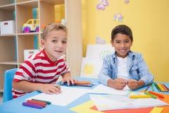 Niños pequeños lindos que dibujan en el escritorio Imágenes de archivo libres de regalías