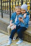 Niños pequeños lindos que juegan con el teléfono celular en ciudad Imagen de archivo libre de regalías