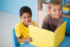 Niños pequeños lindos que leen en el escritorio en sala de clase Fotos de archivo libres de regalías