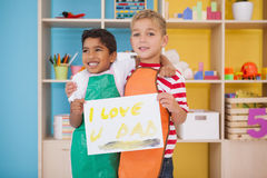 Niños pequeños lindos que muestran la pintura del día de padres Fotos de archivo libres de regalías