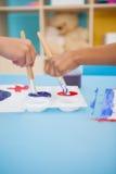Niños pequeños lindos que pintan en la tabla en sala de clase Foto de archivo libre de regalías