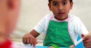 Niños pequeños lindos que pintan en la tabla en sala de clase almacen de metraje de vídeo