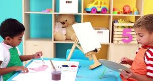 Niños pequeños lindos que pintan en la tabla en sala de clase almacen de video