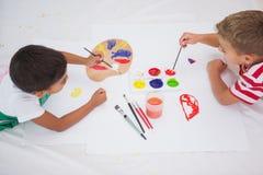 Niños pequeños lindos que pintan en piso en sala de clase Foto de archivo